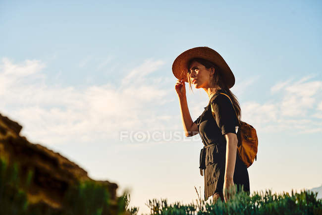 Жіночий турист носити солом'яний капелюх і рюкзак стоячи в природі — стокове фото
