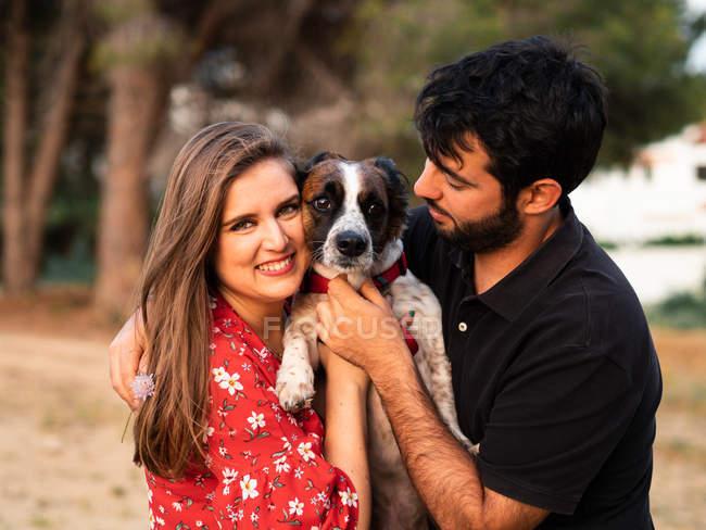 Lächelnfröhliches Paar mit Spaß und halten kleinen Hund unter hohen Gras in der Landschaft — Stockfoto