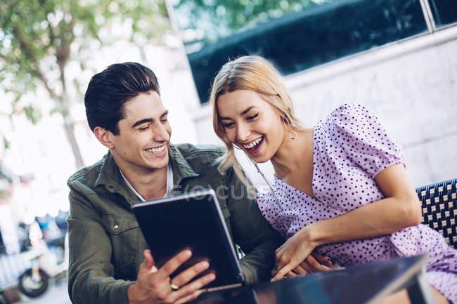 Joyeux jeune couple attrayant en utilisant une tablette numérique en plein air en ville — Photo de stock