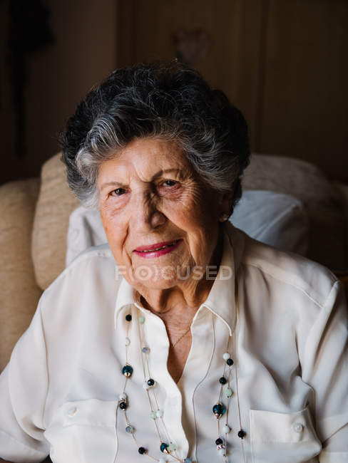 Portrait of happy senior woman in white shirt and with beads on neck looking at camera at home — Stock Photo