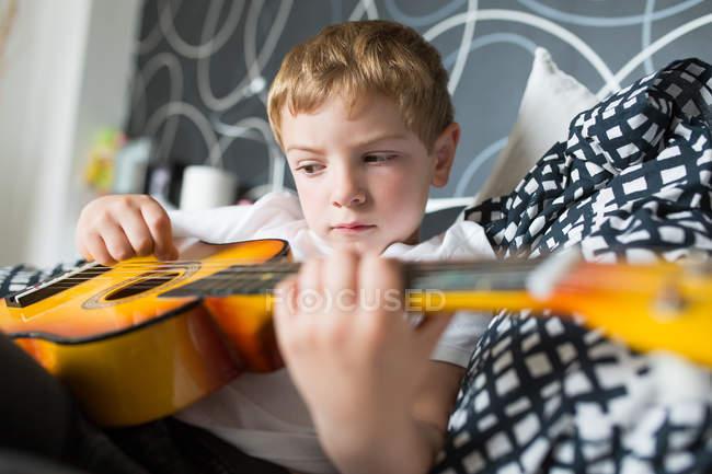 Giovane ragazzo biondo giocare giocattolo chitarra — Foto stock