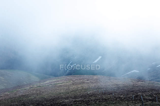 Narrow asphalt road going on mountain slope through thick mist in nature — Stock Photo
