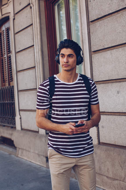 Attractive young man in casual clothes listening music during walking on street in daylight — Stock Photo
