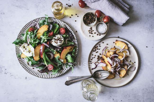 Von oben Teller mit Gourmet-Salaten aus Pfirsichen, roten Zwiebeln, Käse, Öl und schwarzem Pfeffer auf dem Tisch — Stockfoto