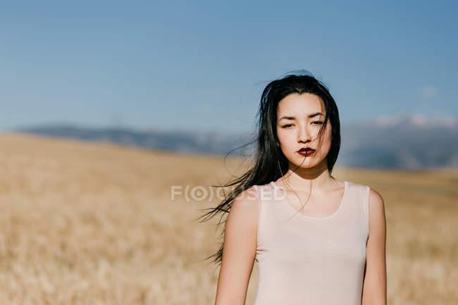 Красивая азиатская женщина смотрит в камеру, стоя на размытом фоне луга в ветреный день на природе — стоковое фото