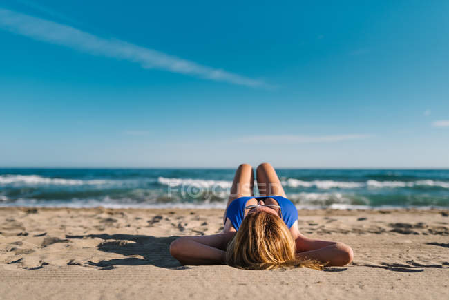 Relaxed woman enjoying good weather lying on sandy beach in bright day — Stock Photo
