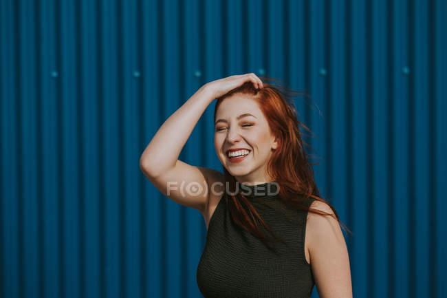 Donna sorridente strizzando gli occhi alla luce del sole e godendo il tempo contro il muro blu — Foto stock