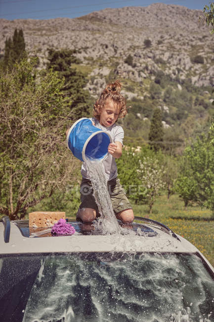 Excited child watering roof of car from blue bucket and washing it with foam sponge — Stock Photo