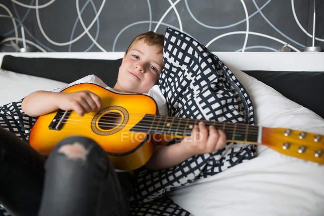 Kleiner blonder Junge spielt Gitarre auf einem Bett — Stockfoto