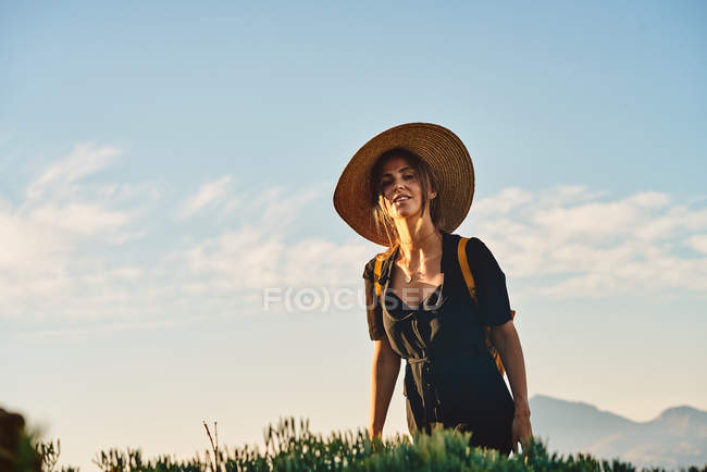 Female tourist wearing straw hat and backpack walking in nature and looking at camera — Stock Photo