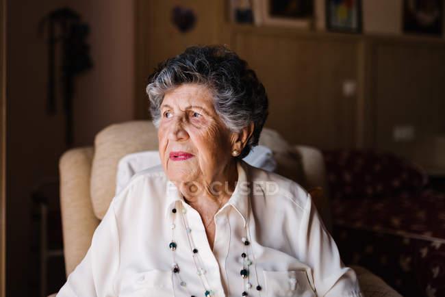 Ritratto di donna anziana felice in camicia bianca e con perline sul collo distogliendo lo sguardo da casa — Foto stock