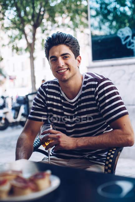Портрет веселого молодого человека в раздетой футболке, смотрящего в камеру, сидящего на террасе с бокалом пива — стоковое фото