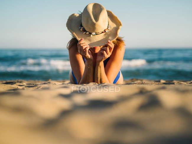 Засмаглий жінка накриваючи обличчям з капелюхом і засмагати на піщаному морському узбережжі в сонячний день — стокове фото