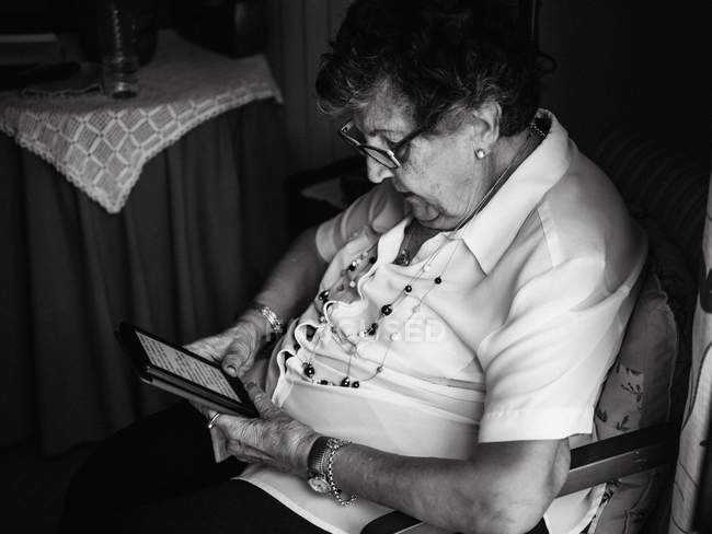 Senior woman in shirt and glasses sitting on armchair and reading e-book in apartment — Stock Photo