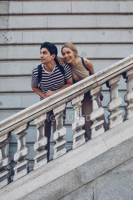 Приваблива пара милуючись видом, стоячи на старих сходах історичної будівлі — стокове фото
