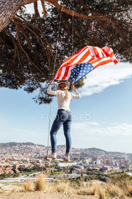Дівчинка святкує 4 липня з американським прапором на гойдалці — стокове фото