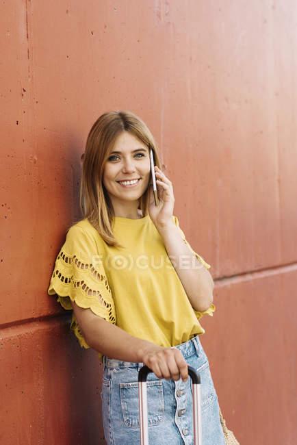 Jeune femme parlant sur téléphone portable appuyé sur le mur rouge — Photo de stock