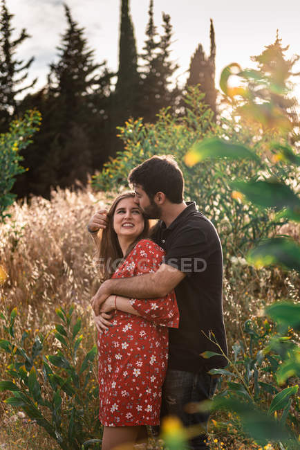 Pensive man hugging smiling pregnant wife on background of picturesque green park in sunny day — Stock Photo