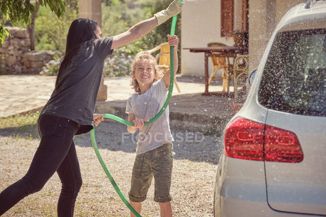 Enthusiastic mother and son spraying water from green hose in yard — Stock Photo