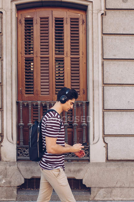 Atractivo joven con ropa casual escuchando música mientras camina por la calle a la luz del día - foto de stock