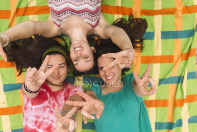 Dall'alto giovani donne adolescenti in abiti luminosi divertirsi e fare il gesto delle dita di pace mentre sdraiato su plaid colorato — Foto stock