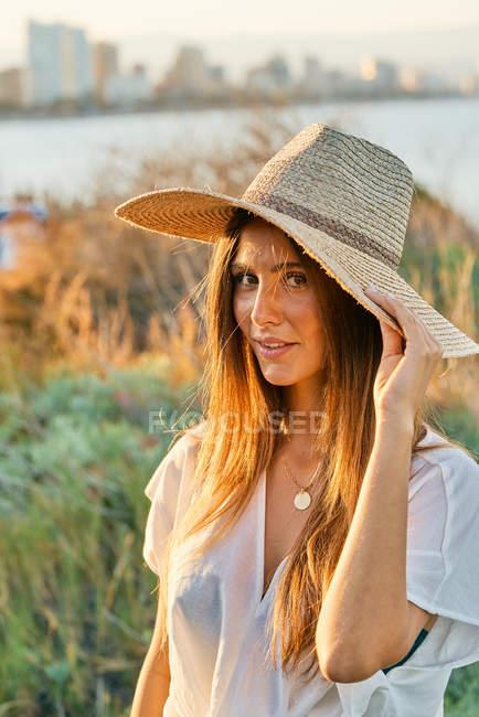 Junge Frau in weißen Kleidern und stylischem Strohhut, die in der Natur lächelnd in die Kamera schaut — Stockfoto