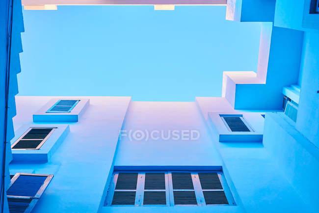 Из низу геометрической лестницы и стен здания в синем цвете — стоковое фото