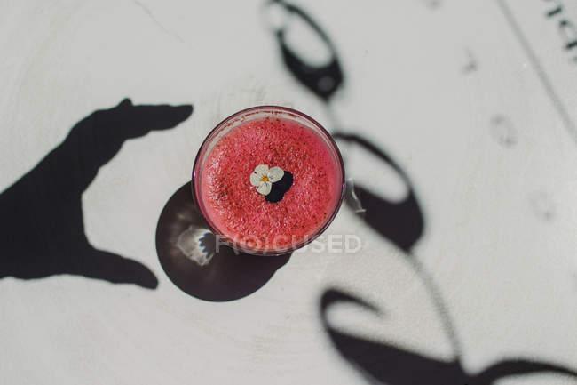 Пузырь пенный вкусный ароматный розовый смузи украшен цветком в стекле на белой поверхности — стоковое фото