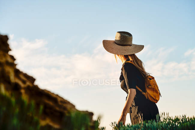 Female tourist wearing straw hat and backpack standing in nature — Stock Photo