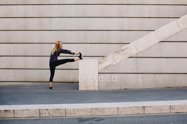 Молода блондинка тягнеться по сходах після бігу. — стокове фото