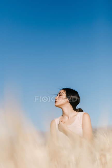 Hermosa hembra asiática mirando hacia otro lado mientras está de pie sobre un fondo borroso de prado en el día ventoso en la naturaleza - foto de stock