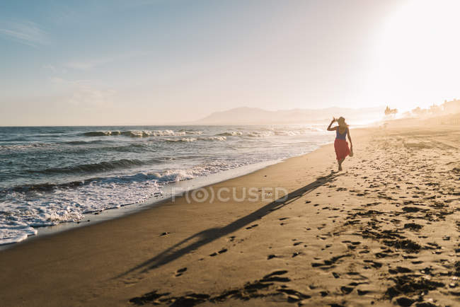 Back view of slim woman in hat and pareo walking along coastline in bright sunlight — Stock Photo
