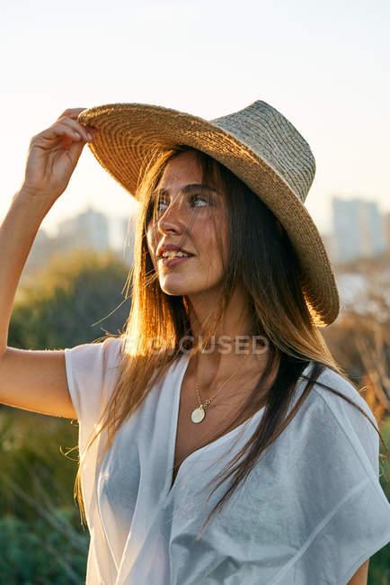 Молода усміхнена жінка в білому одязі та капелюсі дивиться в природі на заході сонця — стокове фото