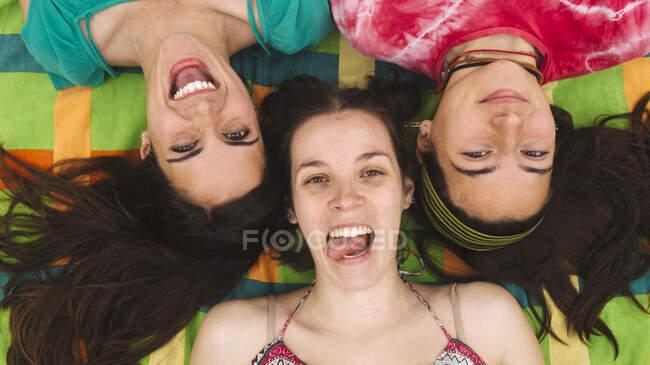 Dall'alto giovani donne adolescenti in abiti luminosi divertirsi e fare facce mentre sdraiato su plaid colorato — Foto stock