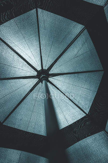 From below view of inside open black umbrella placed against source of light — Stock Photo