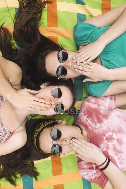 Dall'alto tre giovani donne attraenti in abiti luminosi che si divertono a fare facce serie in occhiali da sole neri sdraiati in una coperta colorata — Foto stock