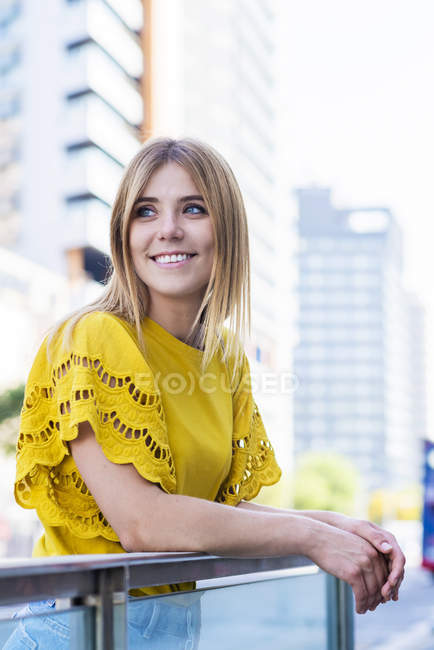 Cheerful elegant young woman smiling and looking away in city — Stock Photo