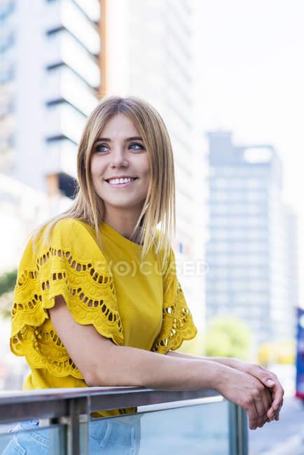 Весела елегантна молода жінка усміхнена і дивиться в місто — стокове фото