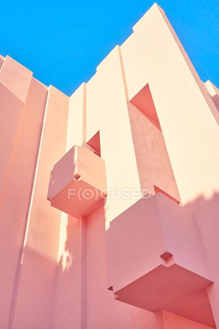 Edifício rosa de forma geométrica complexa sob o céu azul — Fotografia de Stock