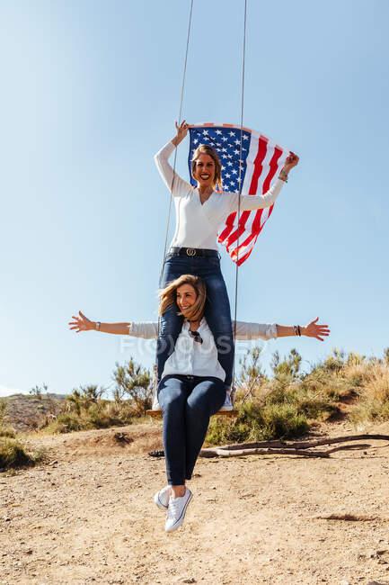 Zwei junge Mädchen mit amerikanischer Flagge feiern den 4. Juli auf einer Schaukel — Stockfoto