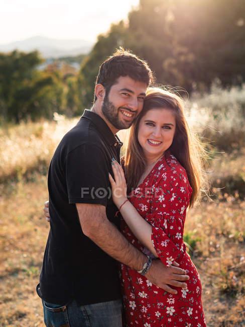 Мужчина, обнимающий беременную женщину на фоне природы в солнечный день — стоковое фото