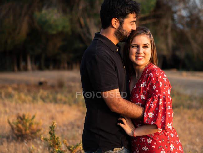 Mann umarmt lächelnde schwangere Frau vor dem Hintergrund der Natur bei sonnigem Tag — Stockfoto