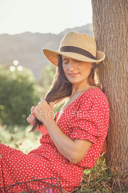 Attractive woman in red dress with hat sitting and thoughtfully looking along in green garden in summer day — Stock Photo