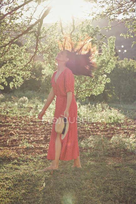 Joven mujer alegre atractiva en vestido rojo bailando y sonriendo en el jardín verde en el día de verano - foto de stock