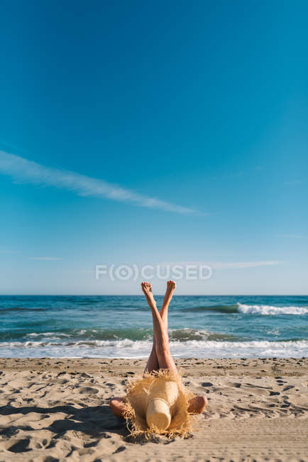 Relaxed woman enjoying good weather lying with raised crossed legs up on sandy beach in bright day — Stock Photo