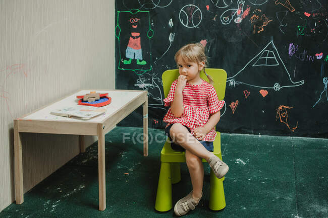 Очаровательный ребенок думает в светло-зеленом кресле со скрещенными ногами в креативной комнате за столом — стоковое фото