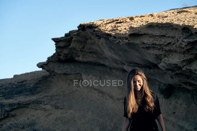 Junge langhaarige stilvolle Frau, die im Sonnenlicht mit Felsen auf dem Hintergrund nach unten schaut — Stockfoto