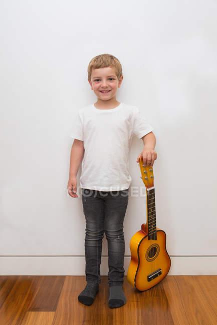 Jeune garçon blonde jouant de la guitare jouet — Photo de stock