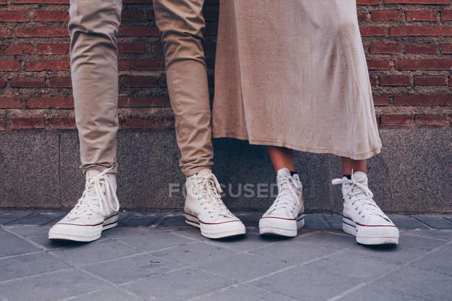 Sección baja de la pareja de pie en la calle junto a la otra - foto de stock