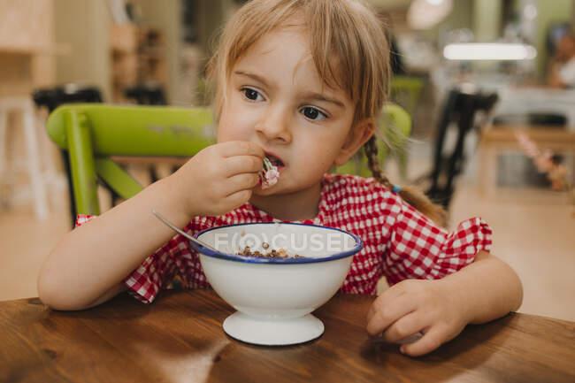 Пристрасні страви з білої миски і чарівної дівчинки, які їдять руками за столом. — стокове фото